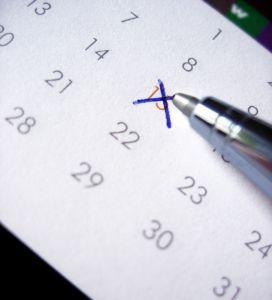 Kynä tekee merkintää kalenteriin.