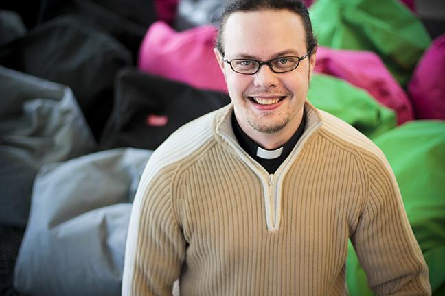 Hymyilevä silmälasipäinen Jussi Koski pantapaidassa, jonka päällä on ruskea neule. Taustalla värikkäitä fatboyta.