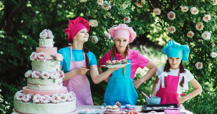 Kolme värikkäisiin leipurin asuihin pukeutunutta lasta seisovat pöydän ääressä, jonka päällä on monikerroksinen täytekakku.