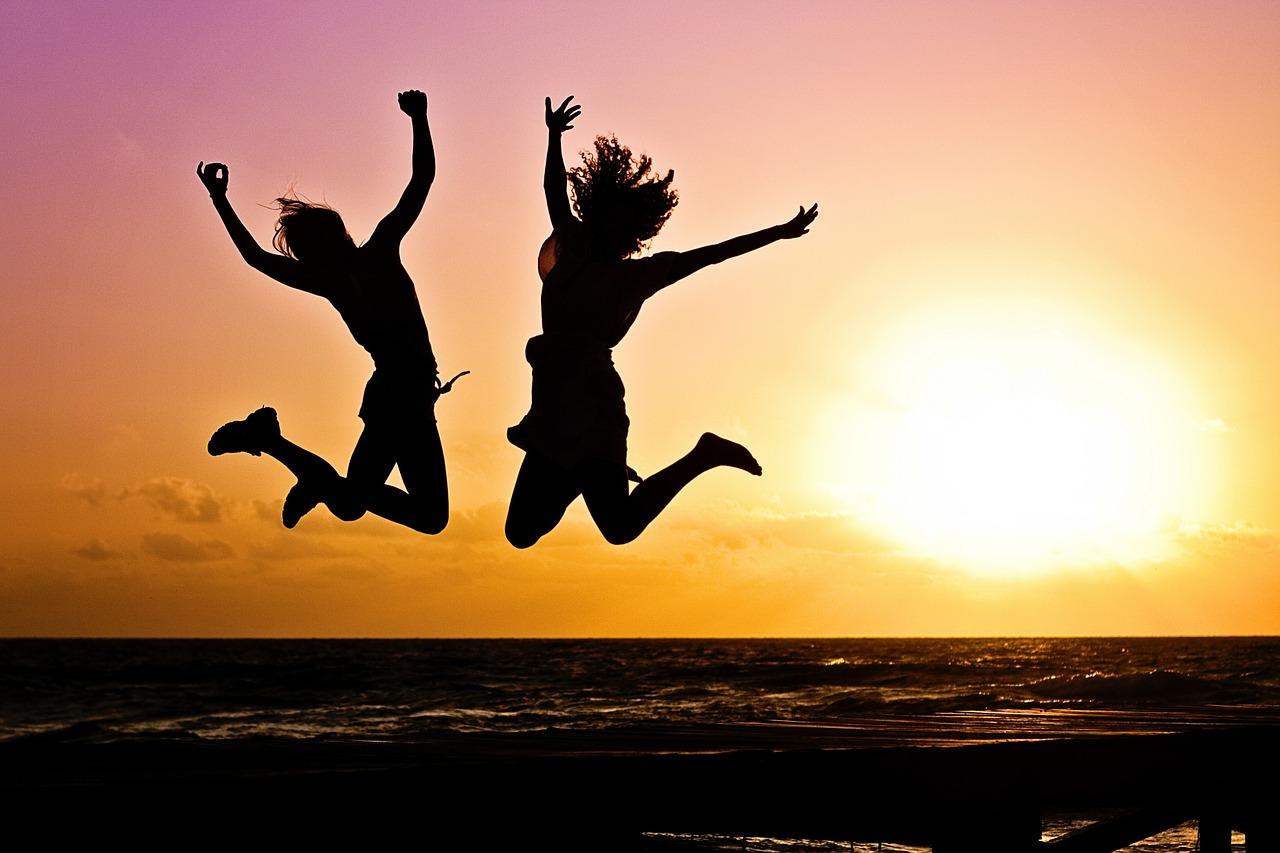 Kahden ilmaan hyppäävän nuoren siluetti vasten auringonlaskua.
