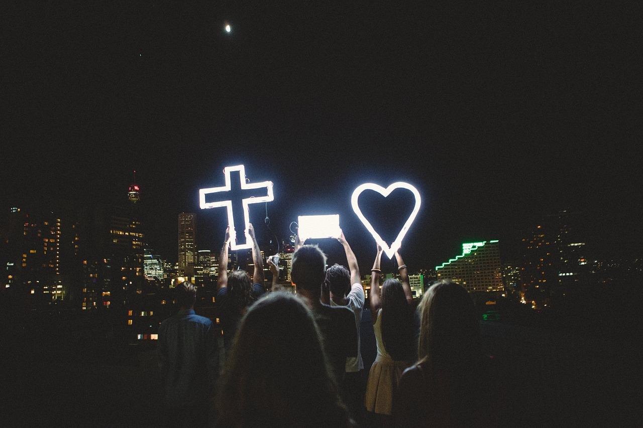 Kolme pimeässä hohtavaa valoa, joissa symbolit sydän, risti ja ankkuri.