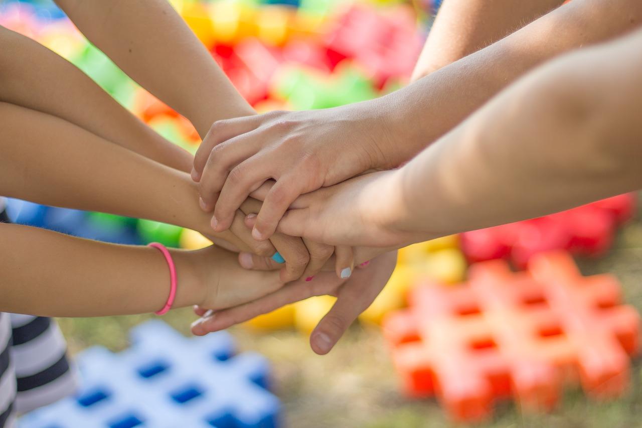 Seitsemän kättä, jotka ovat toistensa päällä värikästä taustaa vasten.