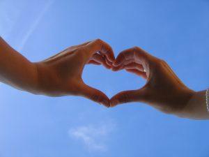 Kädet taivastaustaa vasten muodostavat sormilla sydämen.