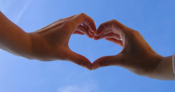 Käsillä muodostettu sydän vasten sinistä taivasta.