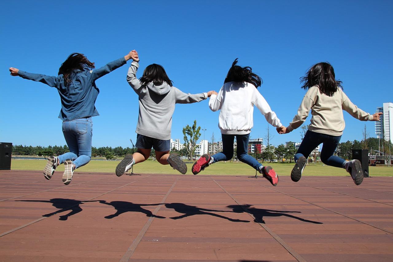 Neljä kouluikäistä lasta hyppää ilmaan urheilukentän juoksuradalla selät kuvaajaan päin.