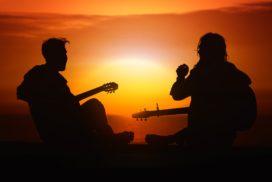 Kahden kitaraa soittavan nuoren siluetti auringonlaskua vasten.