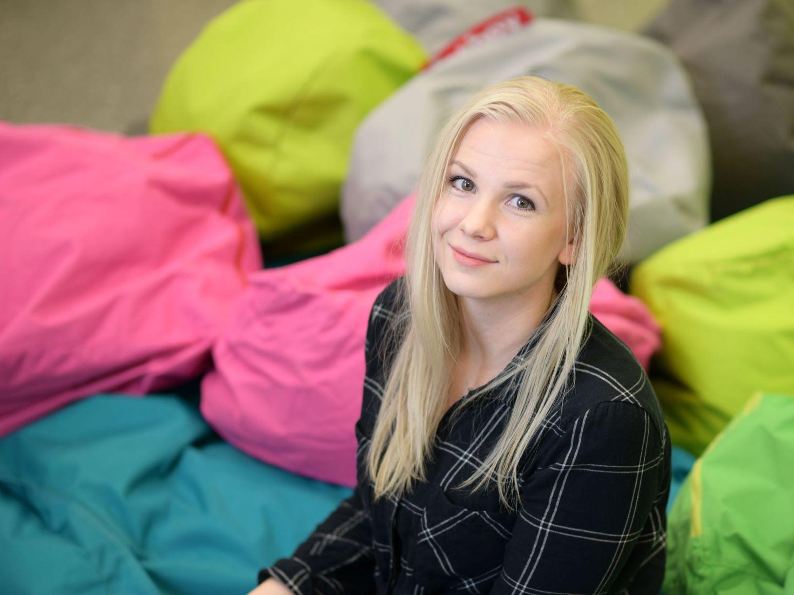Hymyilevä Johanna Flinkman mustaruutuisessa paidassa. Taustalla värikkäitä fatboy tyynyjä.