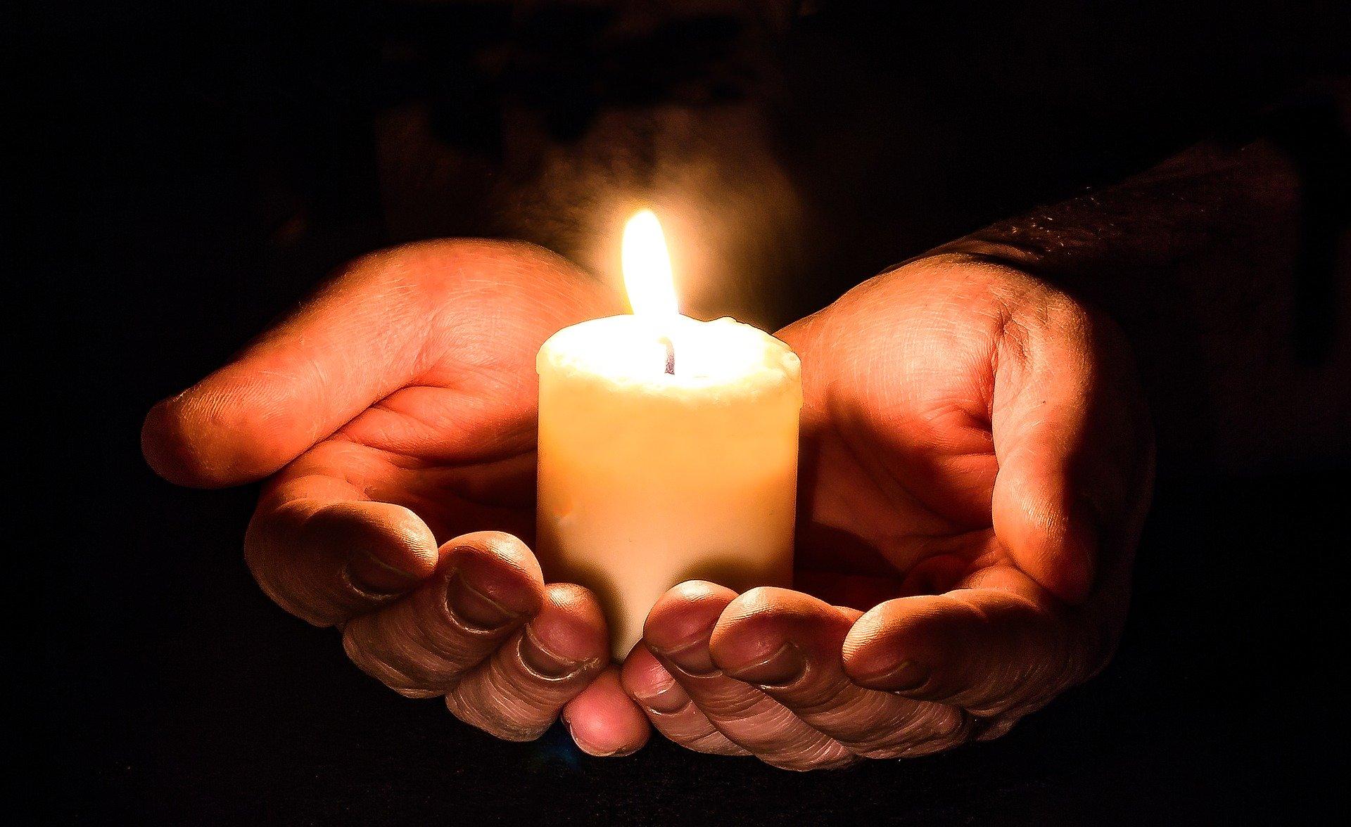 Tummalla taustalla kämmenet, joiden päällä on kynttilä jossa palaa tuli