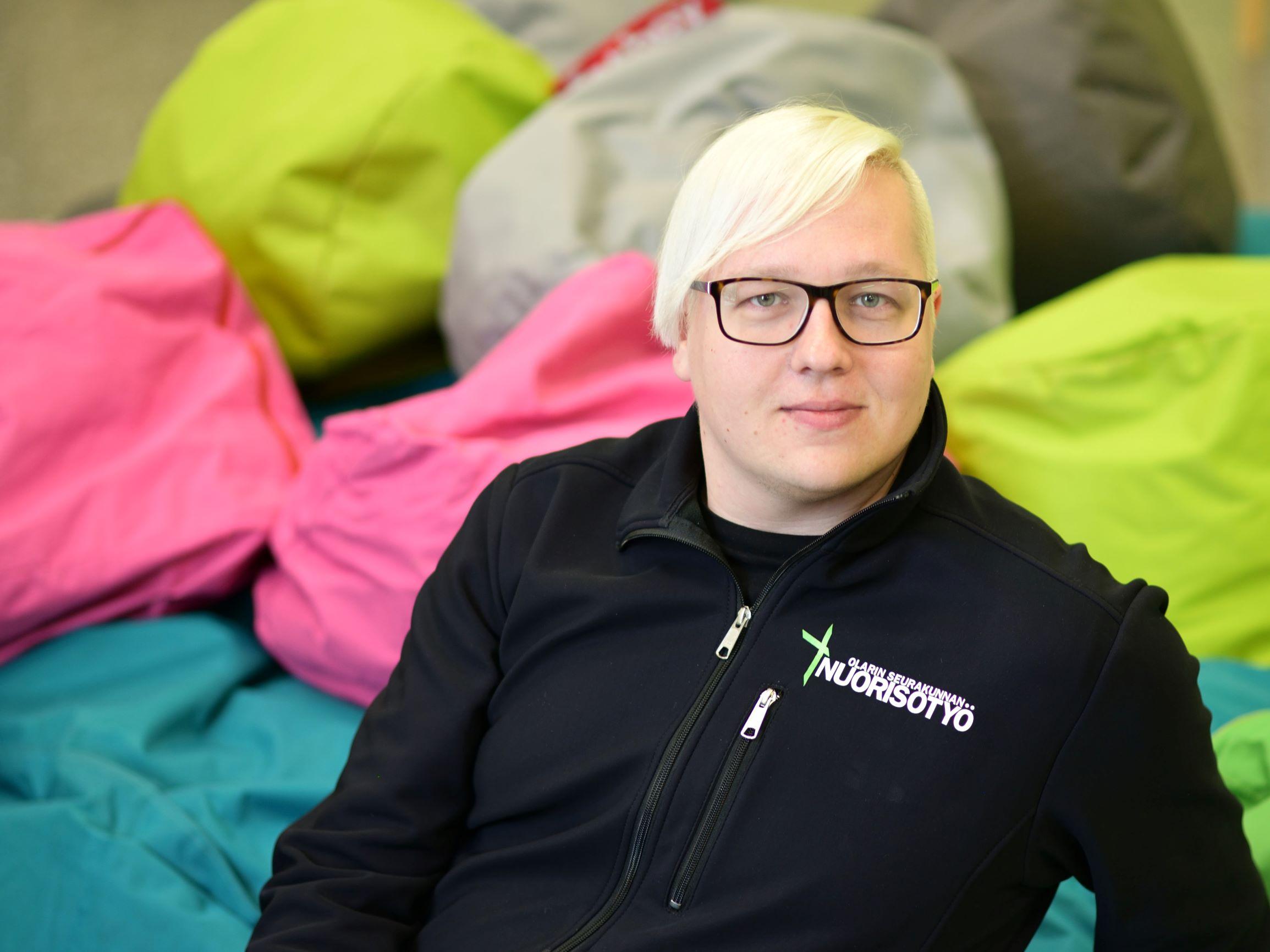 Silmälasipäinen Juha Pohjois-Koivisto nuorisotyön mustassa takissa. Taustalla värikkäitä fatboy tyynyjä.