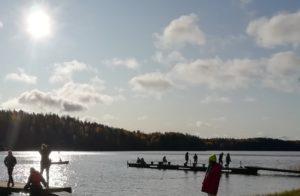 Järvi, jonka takana näkyy metsää. Laitureilla järven päällä on ihmisiä.