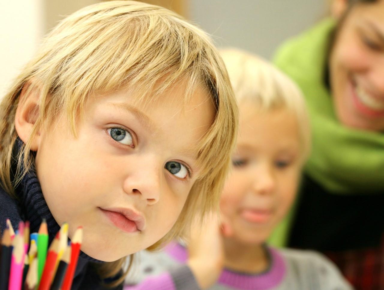 Kaksi vaaleahiuksista lasta, joista toinen katsoo suoraan kameraan. Etualalla kynäpurkki. Taustalla näkyvissä osittain aikuinen.