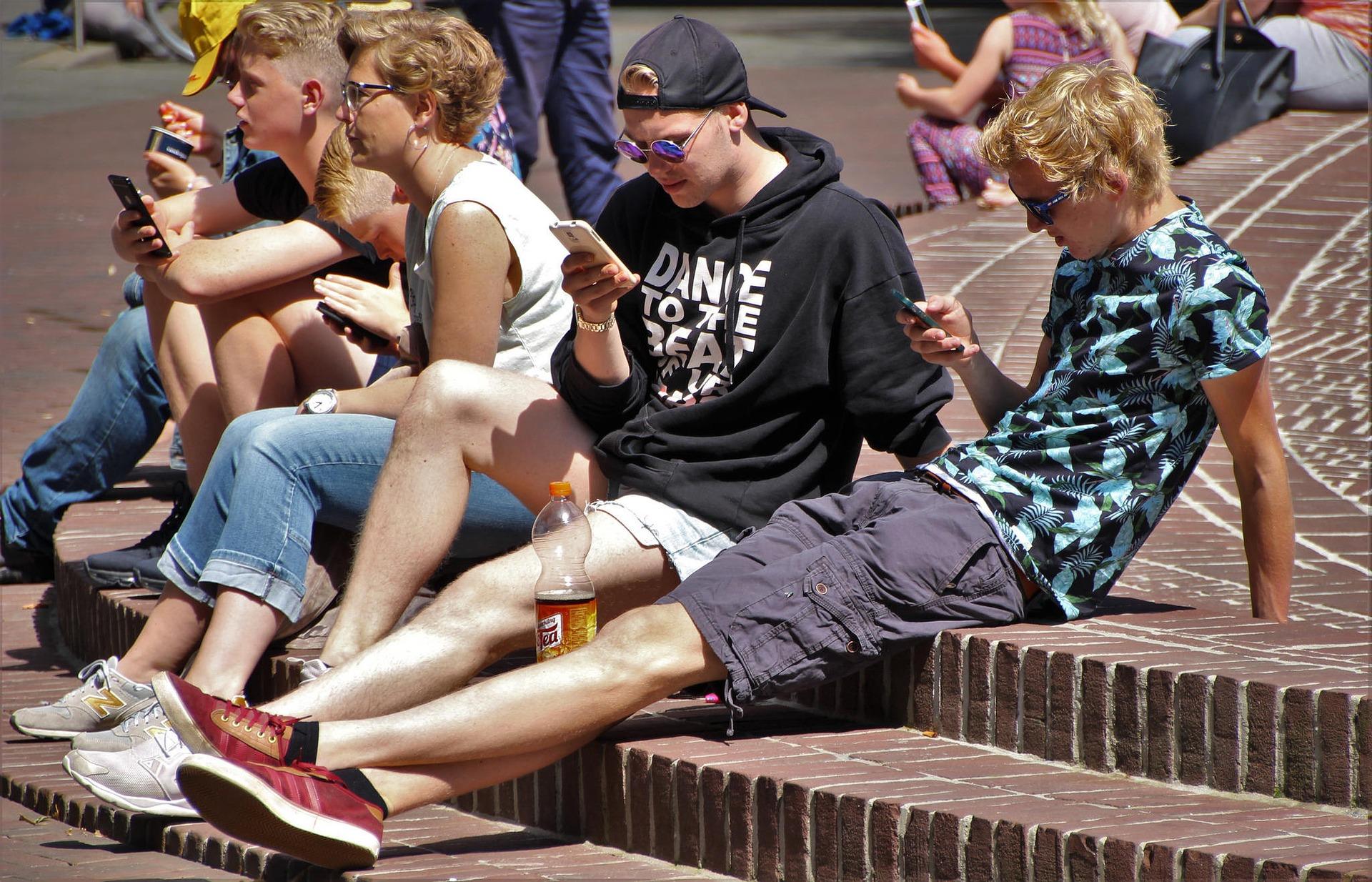 Neljä nuorta ja opettaja istuu tiiliportailla pihalla kesäsäässä. Nuorilla on puhelimet kädessä.