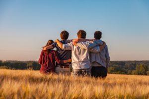 Neljä nuorta pitävät pellolla toisiaan niskan takaa kiinni halaten.