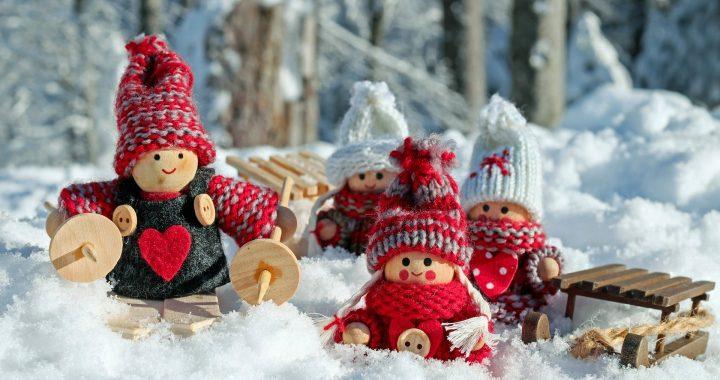 Neljä puunukkea talviasuissaan ja -urheluvälineissään lumen keskellä.
