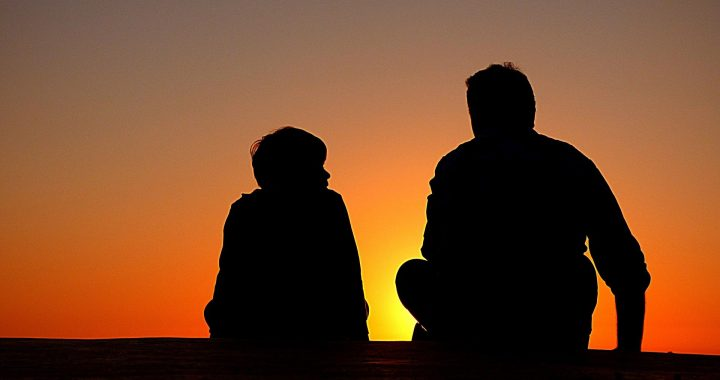 Kuvassa on aikuinen ja lapsi auringonlaskussa.